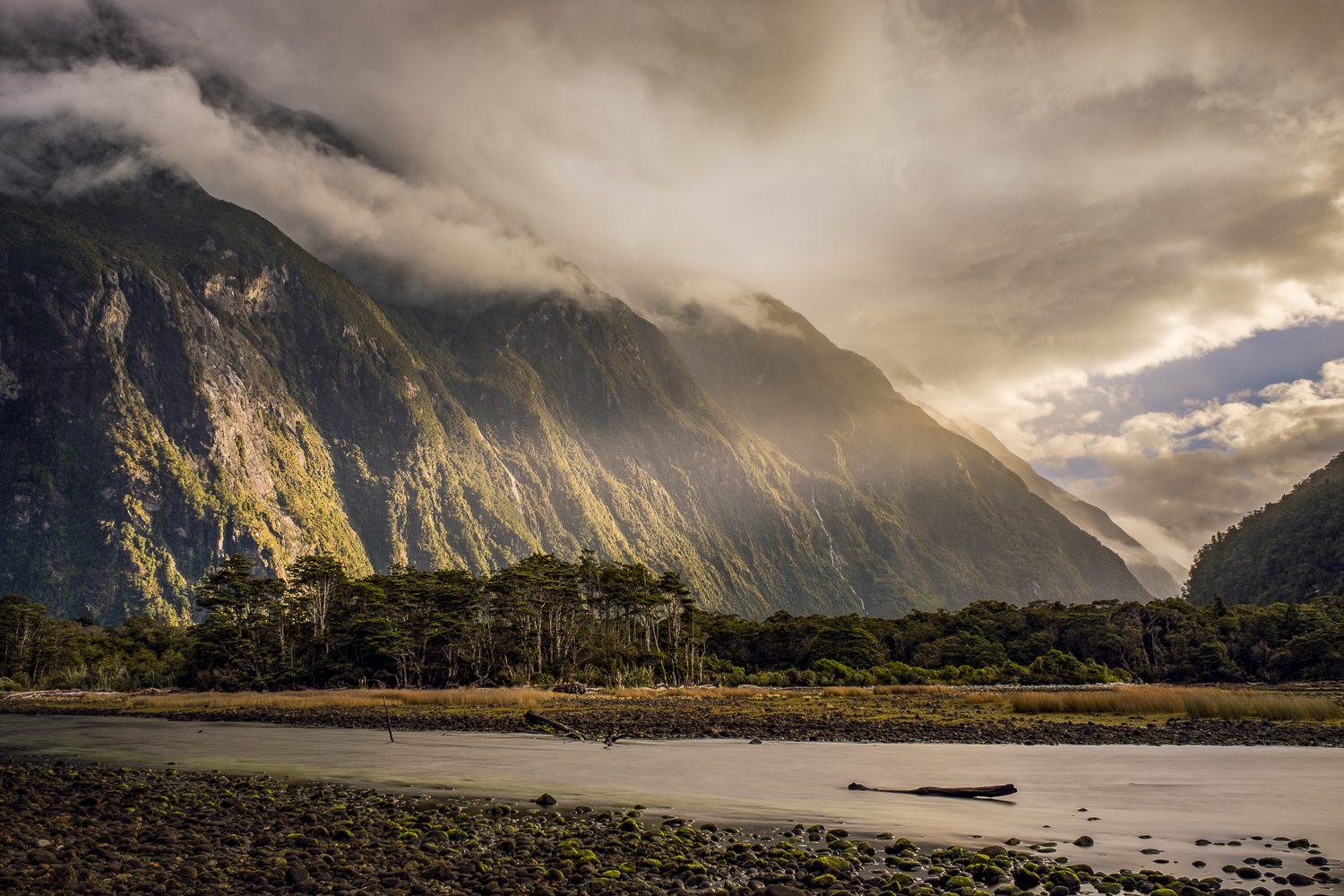 Landscape; Sun rail shines through storm clouds and hits Mountains in Milford Sound, New Zealand
