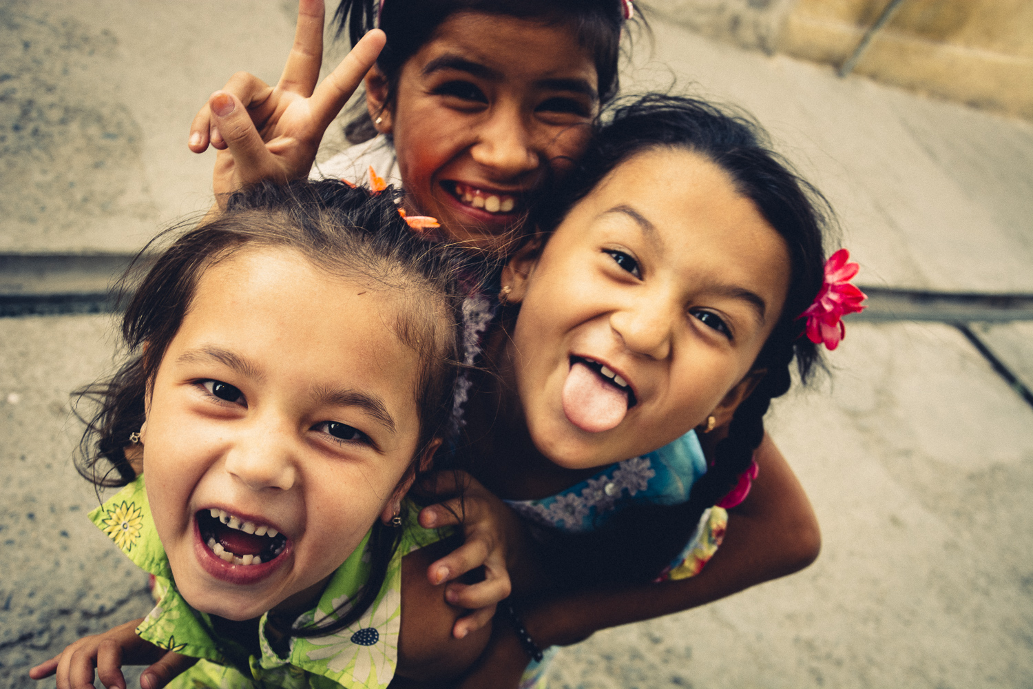 Close up Image of three young girls, laughing into the camera in the jewish quarter in Samarkand, Uzbekistan.