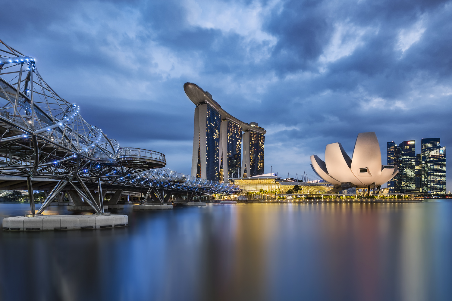 Photograph of the Sandbar, Helix Bridge and the ArtScience Museum in Singapore at night