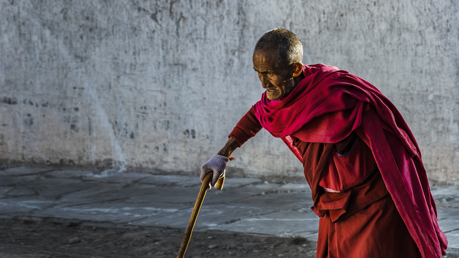 An old Monk in traditional clothes is walking the daily path around the Monastery Labrang in China