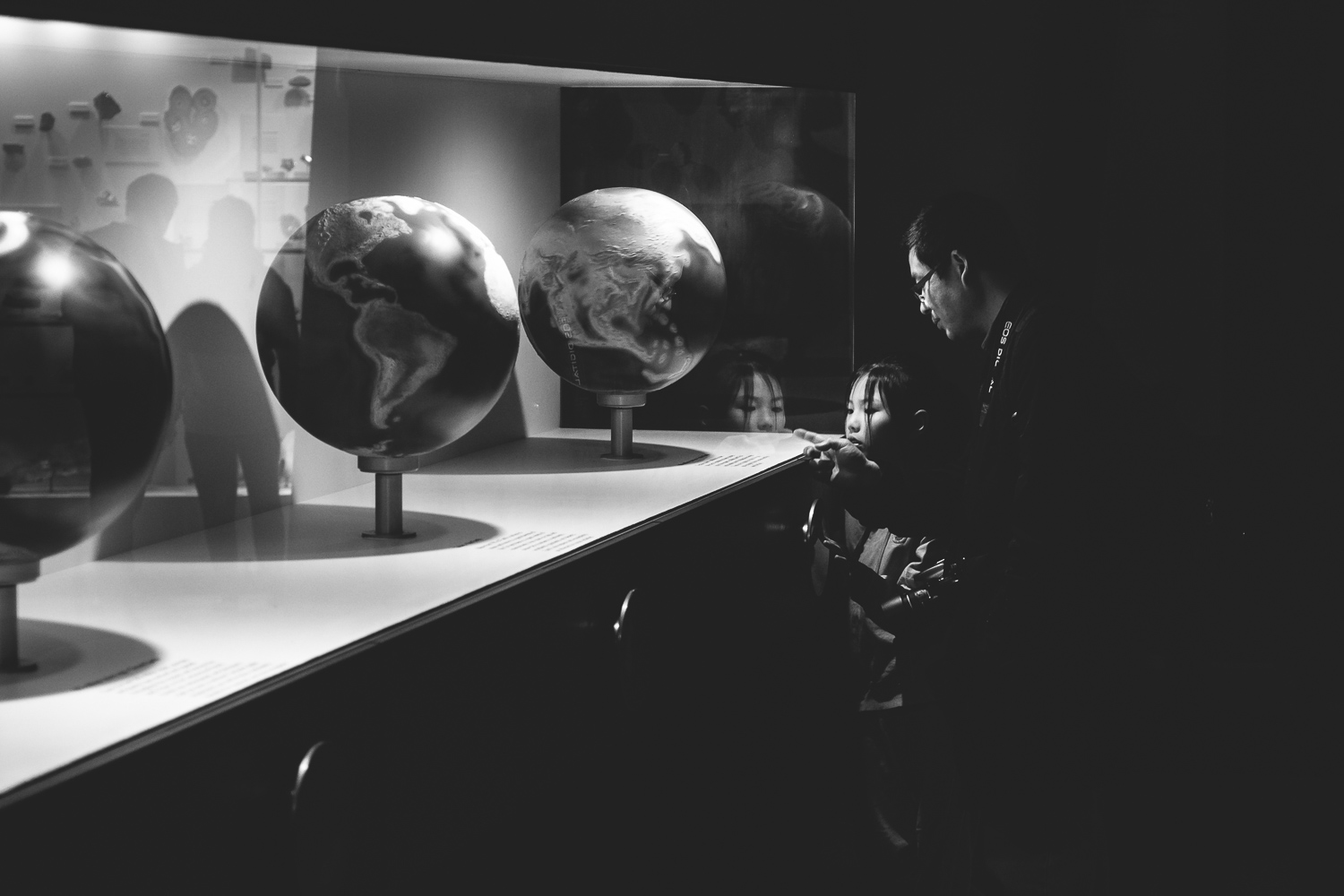 Black and White image of a father explaining something about an exhibition in a museum in Melbourne, Australia