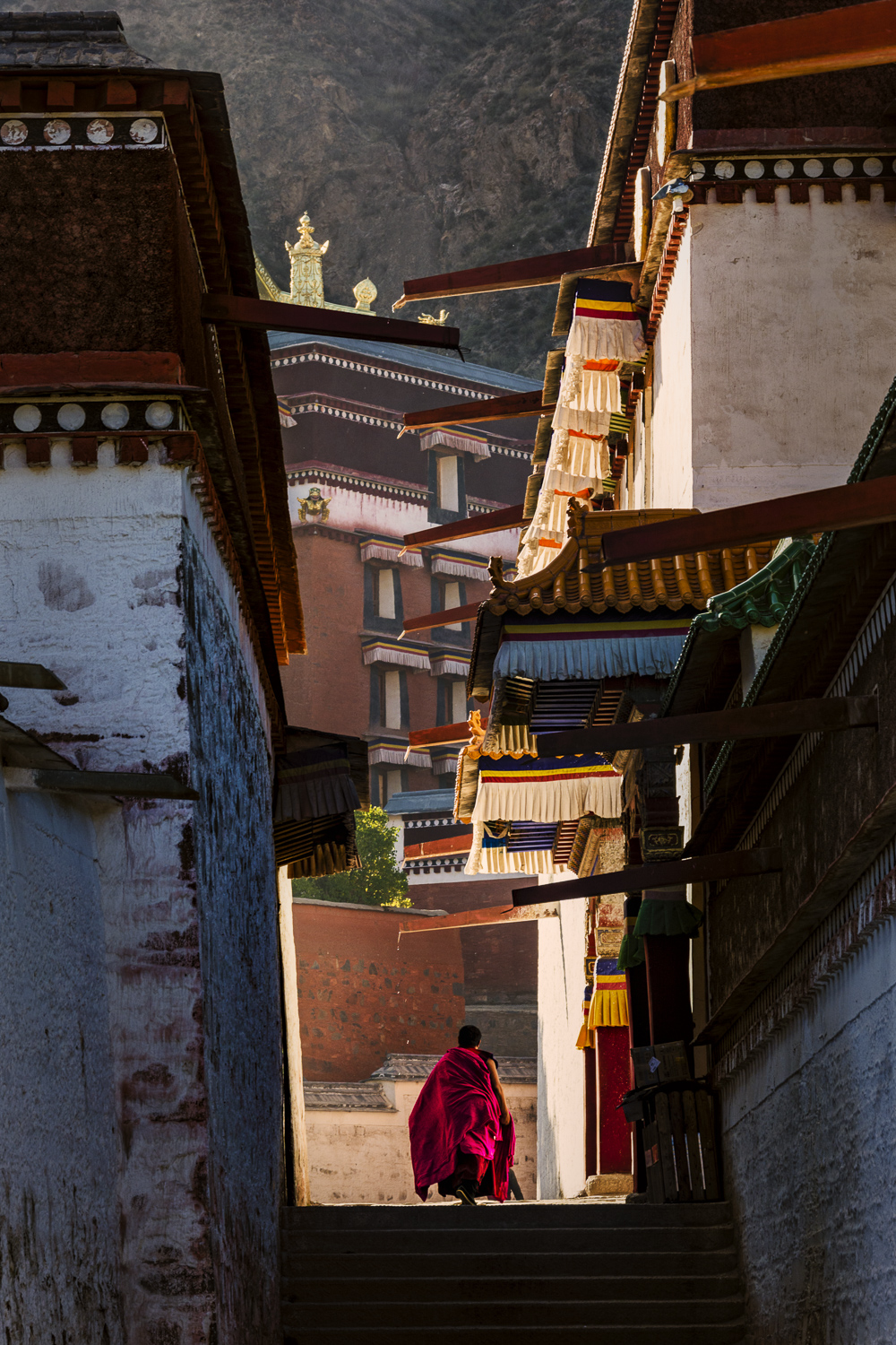 Travel Image of a monk walking between two buildings of the Labrang Monastery in China