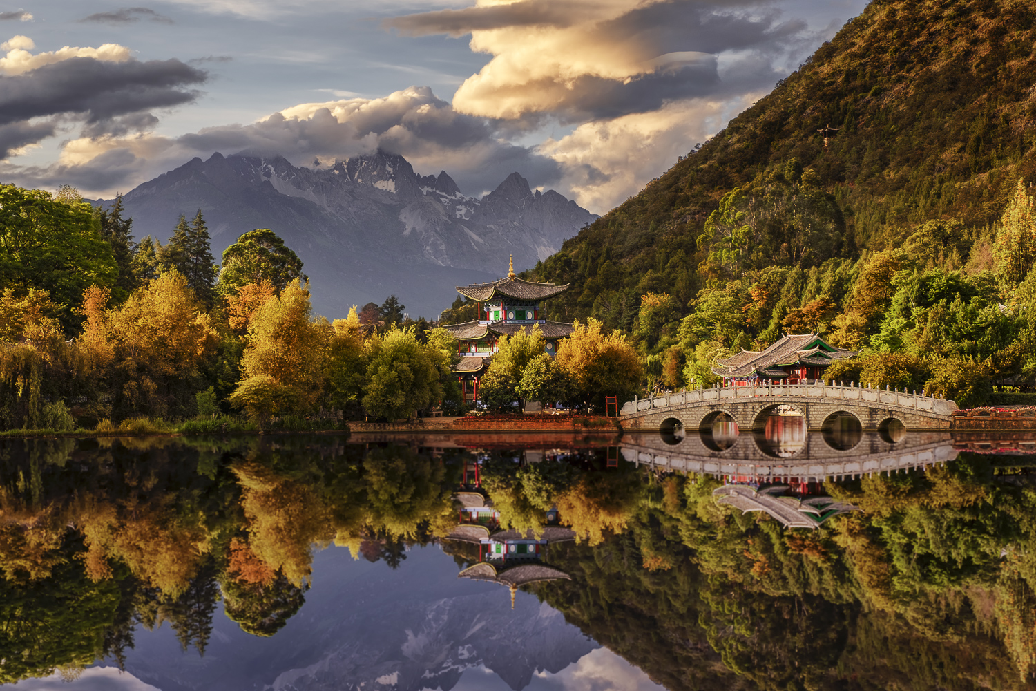 A small temple with a great view of the Jade Dragon Snow Mountain, reflected in the Black Dragon Pool in Lijiang, China